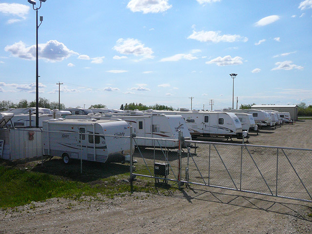 Photo of secure gated entrance at St Albert RV & Boat Storage with many RVs being stored inside.